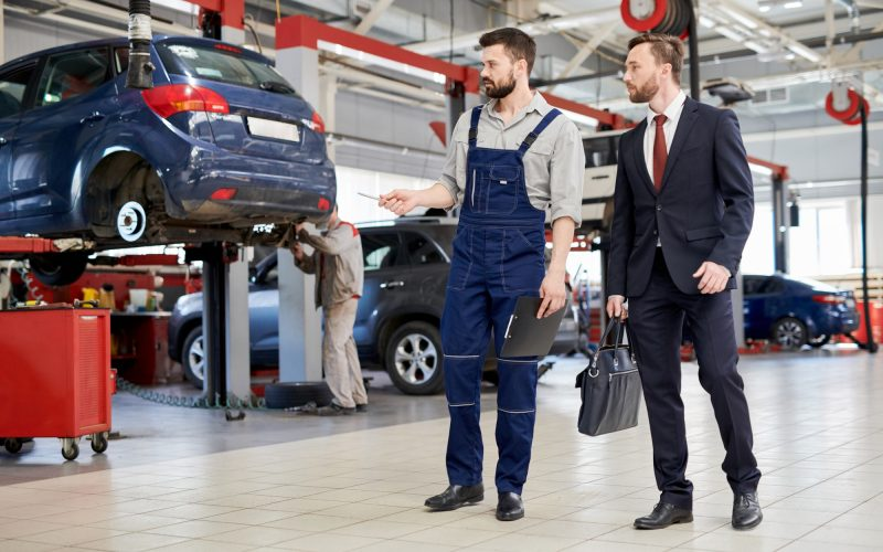 Worker Giving Tour of Car Factory
